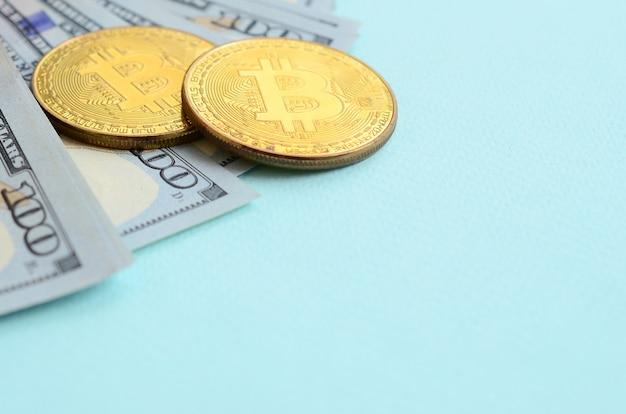 Bitcoins d'or et billets de cent dollars se trouve sur fond bleu clair