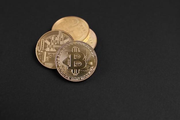Bitcoins or isolés sur fond noir avec espace de copie.