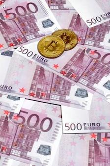 Bitcoins sur pile de billets de cinq cents euros