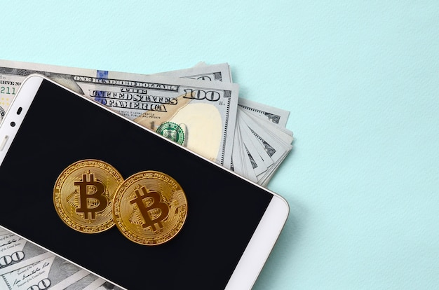 Bitcoins se trouve sur un smartphone et cent billets d'un dollar