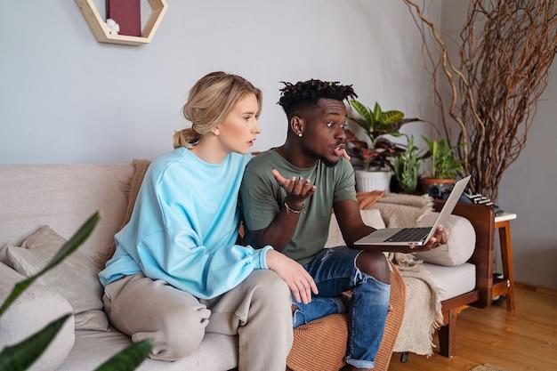 Un black et une blonde sont assis avec un ordinateur portable sur un canapé et sont surpris.