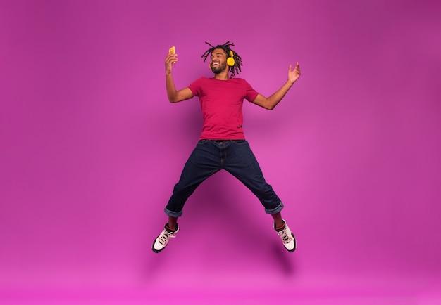 Black boy avec casque jaune écoute de la musique et des danses