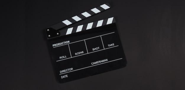 Black clapperboard ou clap board ou utilisation de l'ardoise de film dans la production vidéo, le cinéma, l'industrie du cinéma sur fond noir.