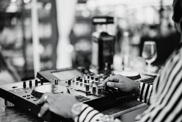 Black dj jouant de la musique au bar à cocktails en plein air - concept de divertissement et de fête - focus sur la main droite