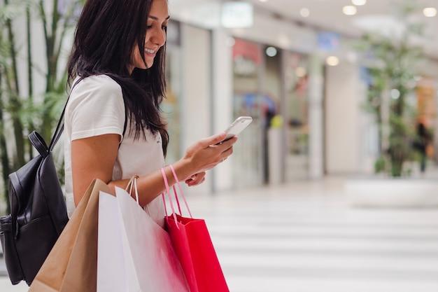 Black friday, femme à l'aide de smartphone et tenant le sac à provisions tout en se tenant sur le centre commercial
