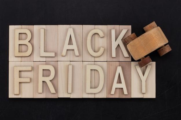 Black friday - texte en lettres en bois sur tableau noir avec voiture en bois. espace de copie.