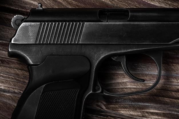 Black gun sur un gros plan en bois. prise de vue en studio. vue de dessus