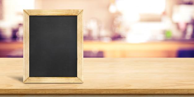 Blackbaord blanc sur le dessus de table en bois de planche avec cuisine à la maison floue