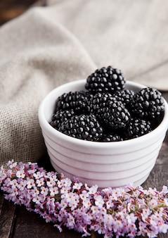 Blackberry dans un bol blanc et des fleurs sur fond en bois.
