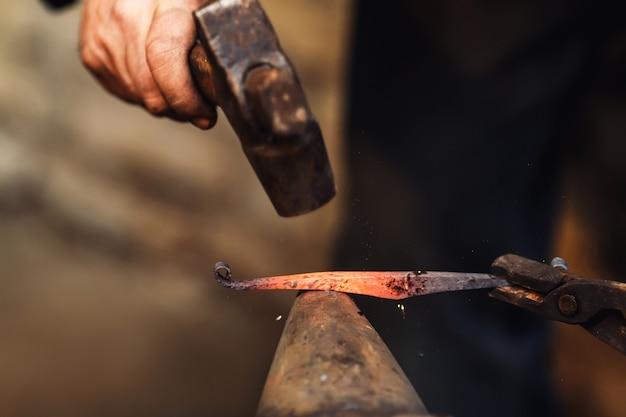 Blacksmith fait un forgeage artistique du métal chaud sur l'enclume.
