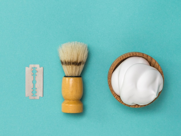 Blaireau et mousse à raser dans un bol en bois. set pour le soin du visage d'un homme. mise à plat.