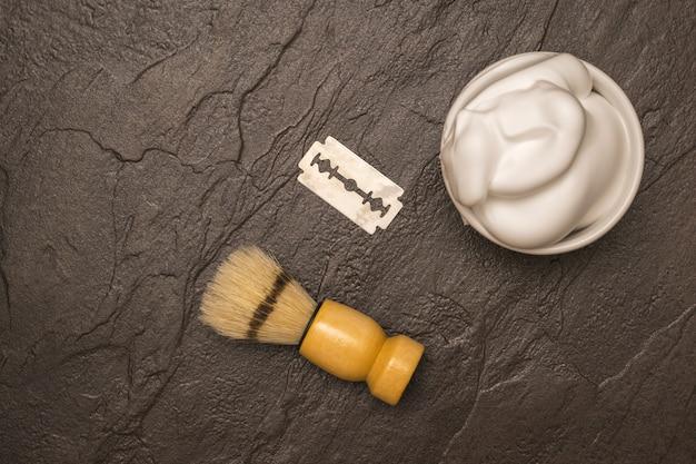 Blaireau, mousse à raser et lame sur une table en pierre. set pour le soin du visage d'un homme. mise à plat.