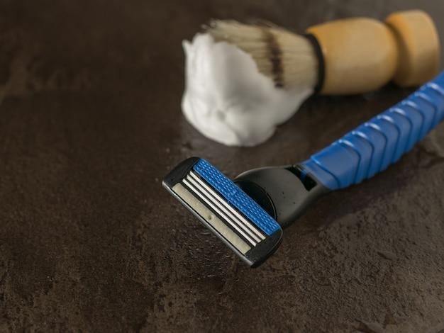 Blaireau avec mousse et rasoir homme bleu sur une table en pierre. set pour le soin du visage d'un homme. mise à plat.