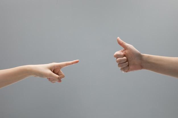 Blâmez et aimez les gestes de la main sur fond gris