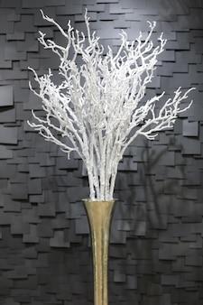 Blanc artificiel fait à la main une branche enneigée dans un pot sur un fond sombre sous forme de tuiles