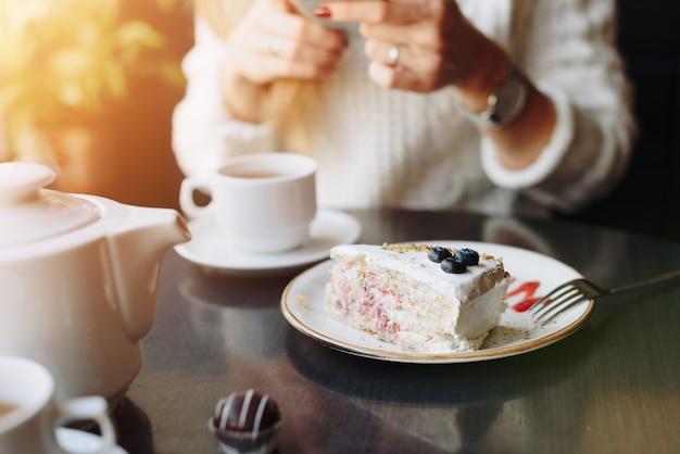 Blanc beau morceau de gâteau aux myrtilles sur une assiette dans un café sur le fond d'une fille avec un smartphone dans un flou