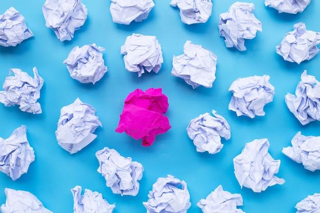 Blanc avec des boules de papier froissé rose sur fond bleu.