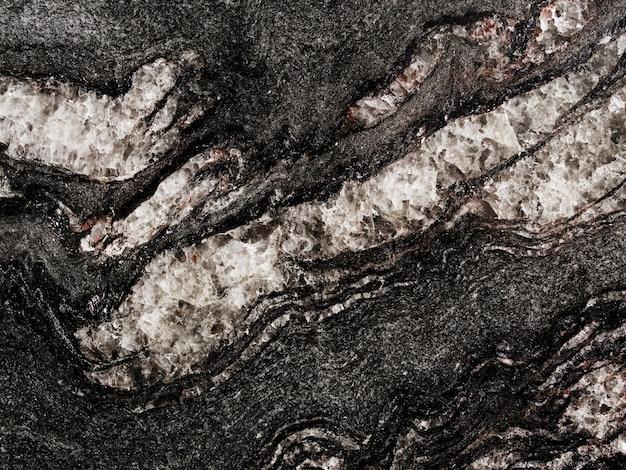 Blanc rugueux texturé sur fond de roche noire