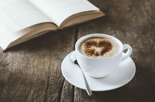 Blanc tasse de café latte art à la cannelle sur une table en bois avec un livre ouvert