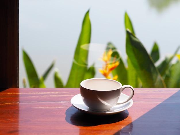 Blanc tasse vide de café sur une table en bois à côté de la fenêtre de verre