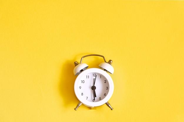 Blanc vieux réveil sur jaune. réveillez-vous à midi.