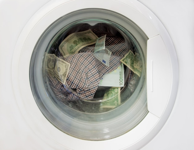 Blanchiment d'argent en dollars et en euros dans une machine à laver avec du linge de maison.