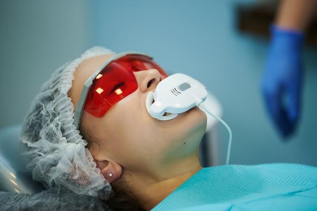 Blanchissement dentaire. femme ayant le blanchiment des dents par dispositif de blanchiment dentaire uv. traitement de blanchiment avec lumière, laser, fluorure.