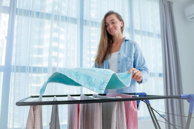 Blanchisserie femme accroche des vêtements mouillés sur sèche-linge après avoir lavé le linge à la maison. les tâches ménagères et l'entretien ménager