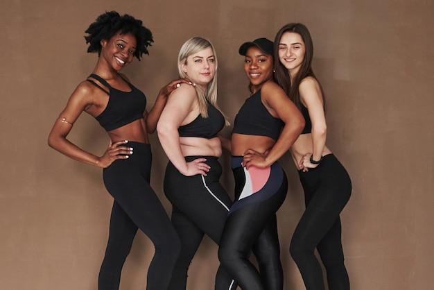 Les blancs et les noirs. groupe de femmes multiethniques debout contre l'espace brun