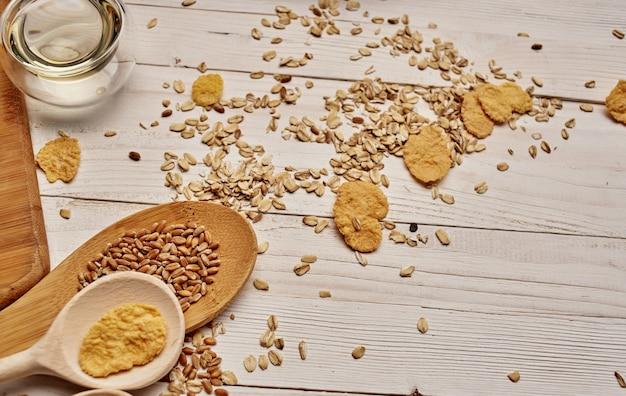 Blé et céréales éparpillés sur la table de cuisine cuillères en bois. photo de haute qualité