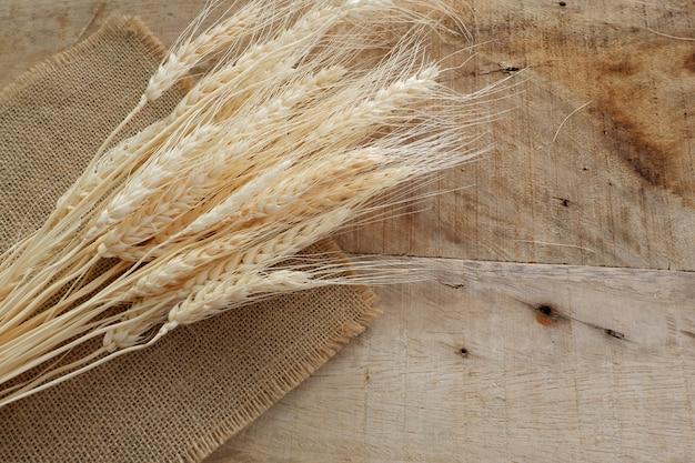 Blé sec et toile de sac sur planche de bois