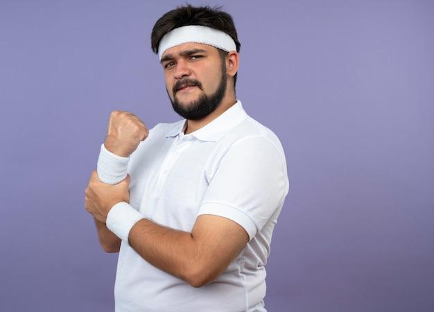 Blessé jeune homme sportif portant bandeau et bracelet a attrapé le bras douloureux isolé sur mur vert