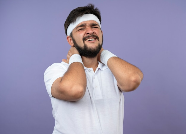 Blessé jeune homme sportif portant un bandeau et un bracelet a attrapé le cou endolori