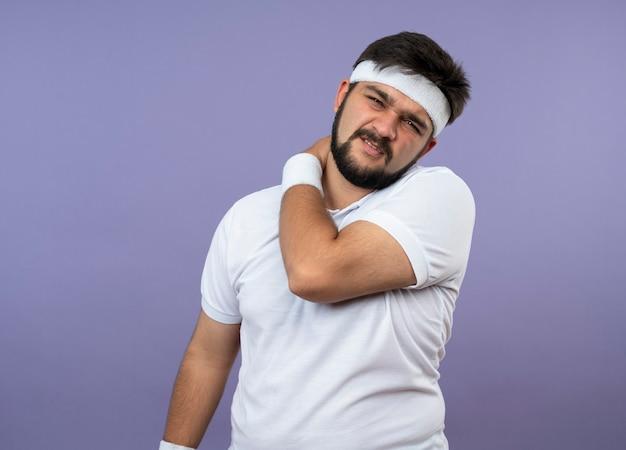 Blessé jeune homme sportif portant un bandeau et un bracelet a attrapé l'épaule douloureuse