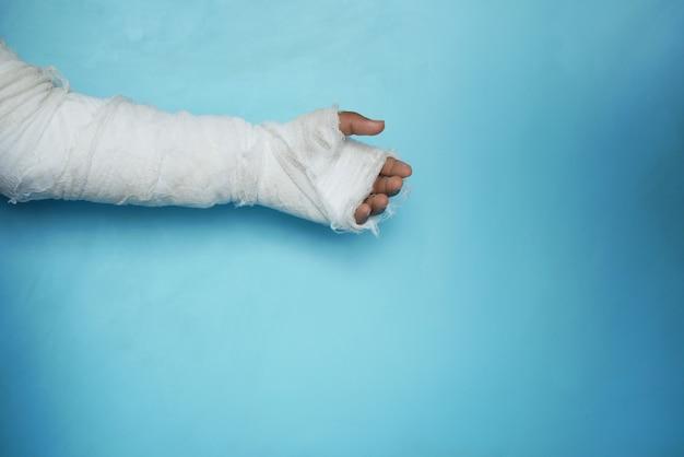 Blessé à la main douloureuse avec un bandage sur fond bleu