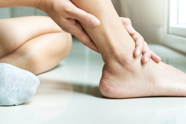 Blessure à la cheville chez les femmes / douloureuse, les femmes touchent la jambe douloureuse à la cheville