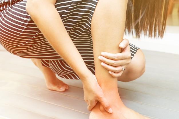 Blessure à la cheville / douloureuse, les femmes touchent la jambe douloureuse