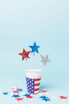 Bleu; accessoires d'étoile rouge et ruban dans le gobelet jetable avec étoiles sur fond bleu