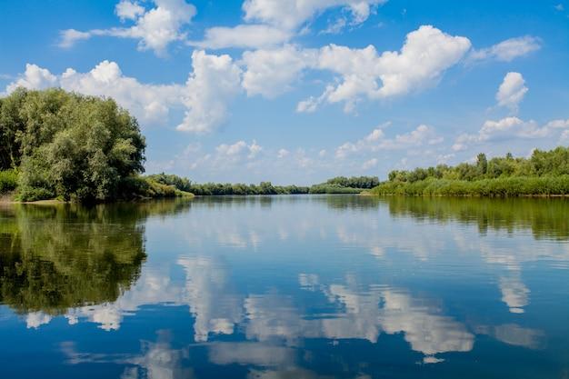 Bleu beau ciel contre la rivière. les nuages sont affichés dans une eau calme. a l'horizon, la rive verte du dniestr, lieu de pêche