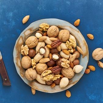 Bleu classique dans les aliments. mélange de noix sur plaque - noix, amandes, noix de pécan, macadamia
