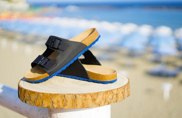 Bleu avec des sandales pour hommes noires sur une bûche de bois en été