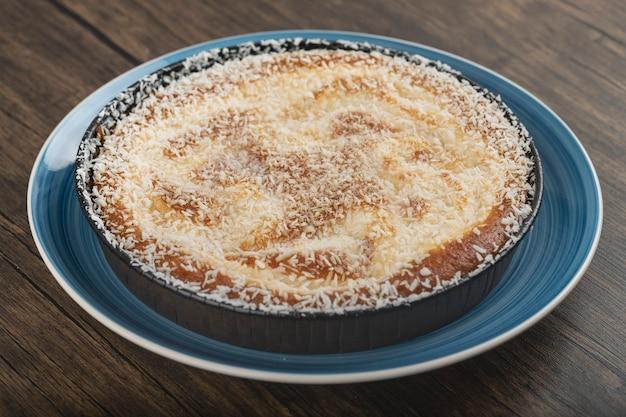 Bleu de tarte sucrée avec des pépites de noix de coco sur une surface en bois