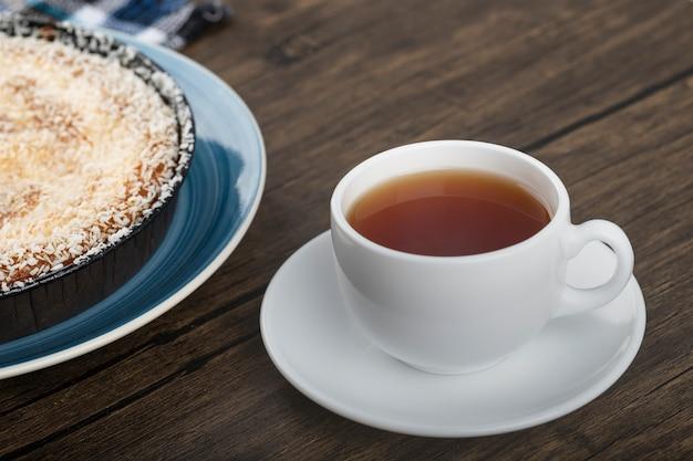 Bleu de tarte sucrée avec des pépites de noix de coco et une tasse de thé sur une surface en bois