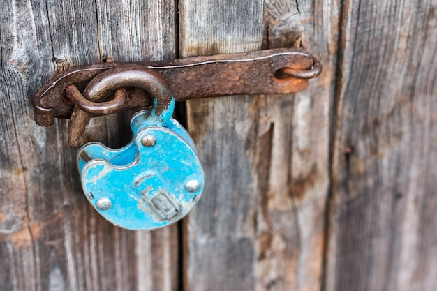 Bleu vieux cadenas déverrouillé rouillé sur porte en bois