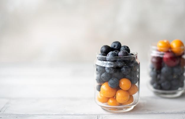 Les bleuets et les baies de physalis dans un bocal en verre