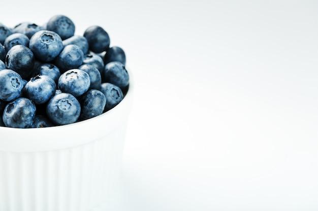 Bleuets dans une tasse blanche sur fond blanc isolé
