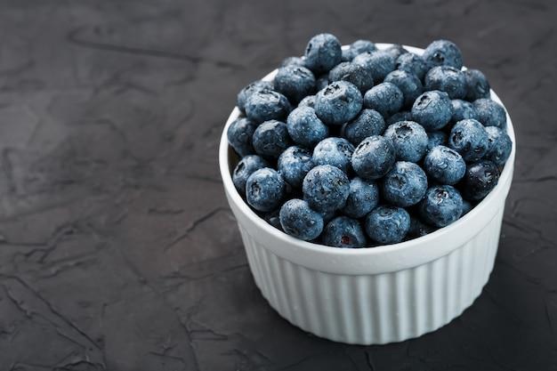 Bleuets dans une tasse blanche sur une texture noire