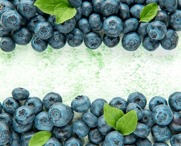 Bleuets fraîchement cueillis sur un fond en bois vert. concept pour une alimentation saine