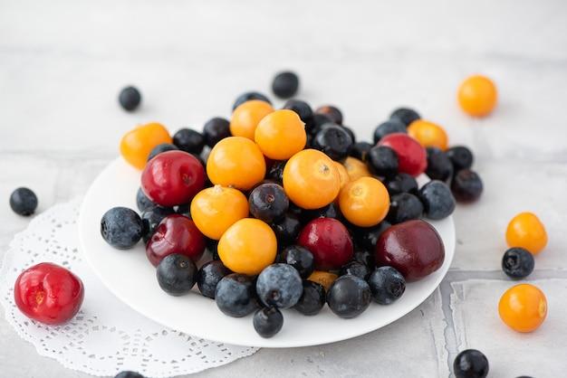 Bleuets frais, baies physalis et cerises sur une plaque blanche