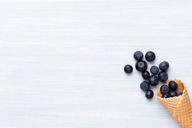 Bleuets frais, dans un bol en forme de coeur sur un fond en bois.